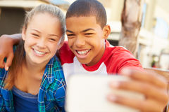 少年夫妇坐在采取Selfie的购物中心的长凳 免版税库存图片