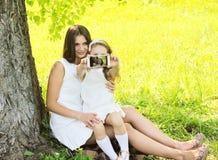 采取在智能手机的母亲和女儿孩子selfie画象 库存图片