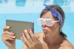 做selfie的女孩由与片剂佩带的吹捧的水池 免版税库存照片