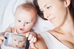 有妈妈的滑稽的女婴在手机做selfie 免版税库存图片