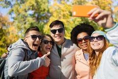 采取与智能手机的微笑的朋友selfie 库存照片