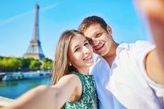 采取selfie的浪漫夫妇在埃佛尔铁塔附近在巴黎 免版税库存图片