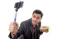 拍与手机照相机和棍子摆在的商人selfie照片满意和成功对金制马上的齿龈和金钱 免版税库存照片