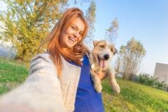 采取selfie的年轻红头发人妇女户外与逗人喜爱的狗 免版税库存图片