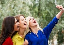 做一selfie的三名妇女在公园 免版税库存照片
