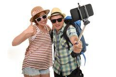 拍与手机的年轻有吸引力和别致的美国夫妇selfie照片隔绝在白色 免版税库存图片