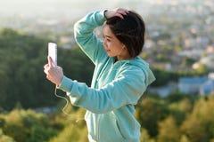 采取selfie的肉欲的年轻日本妇女室外在公园使用她电话和微笑 图库摄影