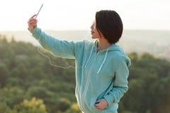 采取selfie的可爱的年轻日本妇女室外在公园使用她电话和微笑 库存照片