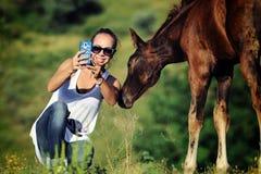 女孩采取与驹的selfie 免版税库存照片