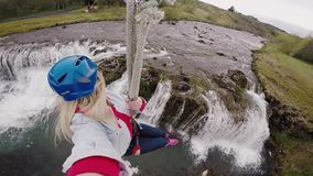 Selfie on action camera of young beautiful woman flying downhill on bungee through the rope way over the river.