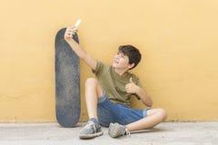 Selfie adolescente joven con el monopatín Fotografía de archivo