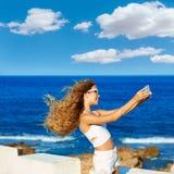 Selfie adolescente rubio de la foto de la muchacha en smartphone en la playa Fotografía de archivo libre de regalías