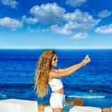 Selfie adolescente rubio de la foto de la muchacha en smartphone en la playa Foto de archivo libre de regalías