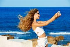 Selfie adolescente rubio de la foto de la muchacha en smartphone en la playa Imagen de archivo