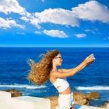 Selfie adolescente rubio de la foto de la muchacha en smartphone en la playa Fotos de archivo