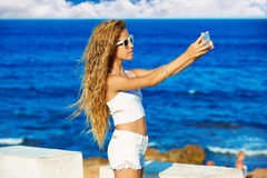 Selfie adolescente rubio de la foto de la muchacha en smartphone en la playa Imagen de archivo libre de regalías