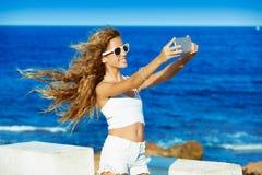 Selfie adolescente rubio de la foto de la muchacha en smartphone en la playa Fotos de archivo libres de regalías
