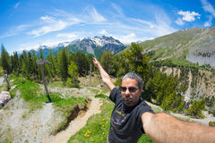 Selfie of adult hiker on top of trail crossing high altitude conifer woodland with snowcapped mountain range in background and moo Royalty Free Stock Images