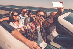 Selfie again!. Group of young happy people enjoying road trip in convertible and making selfie Stock Photo