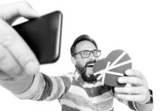 Selfie of attractive, crazy bearded man in jeans shirt with heart over white background. Portrait of happy man in glasses standing stock photography