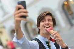 Selfie av den stiliga unga mannen som äter glass Royaltyfria Bilder
