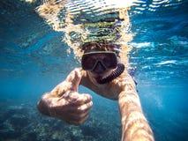 Selfie av den unga mannen som snorklar i havet, tumme upp royaltyfri foto