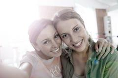 Selfie av två gladlynta flickvänner arkivfoton