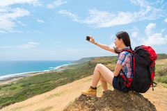 Selfie backpacker tourist sitting on the mountain. Selfie backpacker tourist sitting on mountain happy with beautiful scenery taking pictures through mobile Stock Photos