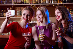 Selfie in the bar. Lovely girls are taking a selfie in the bar stock photos