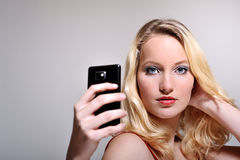 Selfie. Beautiful woman posing for a selfie with a smart phone. Very crisp, her eyes are in focus Stock Images