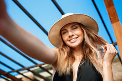 Selfie of beautiful young cheerful girl in hat rests at morning beach Royalty Free Stock Photo