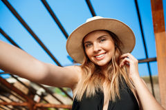 Selfie of beautiful young cheerful girl in hat and sunglasses rests at morning beach Royalty Free Stock Images
