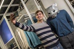 Selfie beim Einkauf Ein Kerl in einer gestreiften Strickjacke in einem Speicher mit Kleidung macht Fotos von am Telefon nahe bei lizenzfreie stockbilder