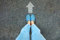 Selfie Blue Shoes and Blue Jeans. Female Feet Standing with White Arrow Line on Road Cement Background Royalty Free Stock Images