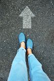 Selfie Blue Shoes and Blue Jeans. Female Feet Standing with White Arrow Line on Road Cement Background Stock Photo