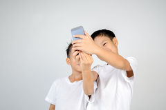 Selfie brother. Two asian white shirt boy use smartphone for selfie together. On white background Royalty Free Stock Image
