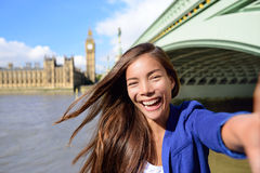 Selfie businesswoman at Big Ben - London travel. London travel selfie businesswoman. Joyful young casual business woman smiling at camera with Thames river, Big Royalty Free Stock Images