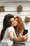 Selfie at the cafe. Beautiful young women take selfie with mobile phone, while sitting at cafe Stock Photography