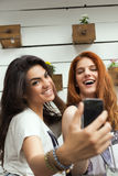 Selfie at the cafe. Beautiful young women take selfie with mobile phone, while sitting at cafe Stock Photos