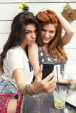 Selfie at the cafe. Beautiful young women take selfie with mobile phone, while sitting at cafe Royalty Free Stock Photos