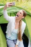 Selfie camping woman in tent taking self portrait using camera smartphone. Selfie camping woman in tent taking self portrait using camera smartphone Stock Image