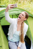 Selfie camping woman in tent taking self portrait using camera smartphone. Selfie camping woman in tent taking self portrait using camera smartphone Royalty Free Stock Photos