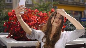 Selfie castana sbalorditivo delle prese sul suo telefono che si siede nel ristorante prima dei fiori rossi stock footage