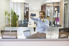 Selfie casual businessman taking pictures in open space office. Businessman taking a picture of himself at work Stock Image