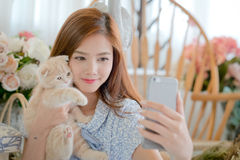 Selfie cat with a cute little girl . On a bright day Royalty Free Stock Photography