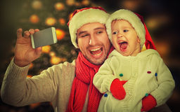 Selfie  in Christmas. happy family dad playing with daughter and photographed on  mobile phone Royalty Free Stock Photo