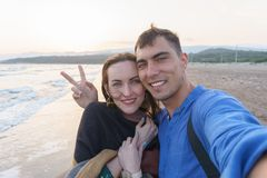 Selfie couple in love on the beach at sunset with a symbol of peace. Selfie smiling couple in love on the beach at sunset with a symbol of peace. Concept of stock images