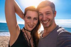 Selfie couple with sun. Joyful couple looking camera doing selfie royalty free stock images