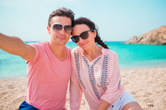 Selfie couple taking pictures on the beach in Cyclades. Tourists people taking travel photos with smartphone on summer. Selfie couple taking pictures at Mykonos Royalty Free Stock Photo
