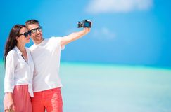 Selfie couple taking pictures on the beach. Tourists people taking travel photos on summer holidays. Selfie couple taking pictures on the beach. Tourists people royalty free stock photography